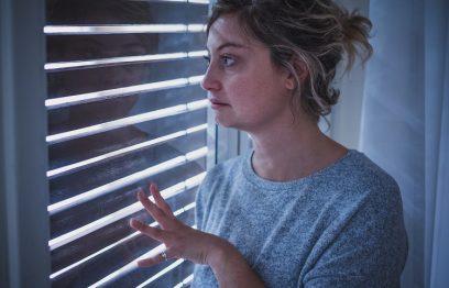 Woman peeks through blinds