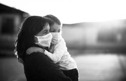 Woman holds toddler outdoors- both wear protective cloth face masks