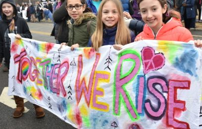 """Four teenagers hold a cloth """"Together we rise"""" banner"""