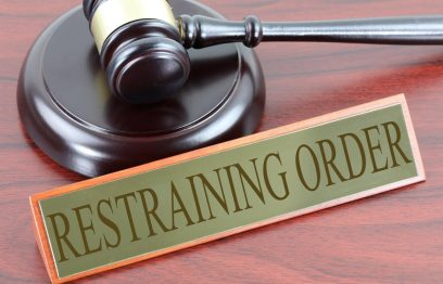 """Gavel and sound board labeled """"Restraining order"""""""