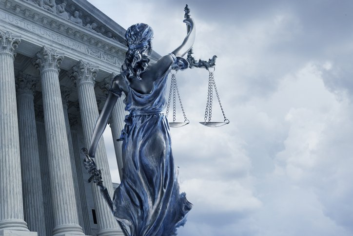 A statue of the blindfolded lady justice in front of the United States Supreme Court building. A clouded sky fills the background.