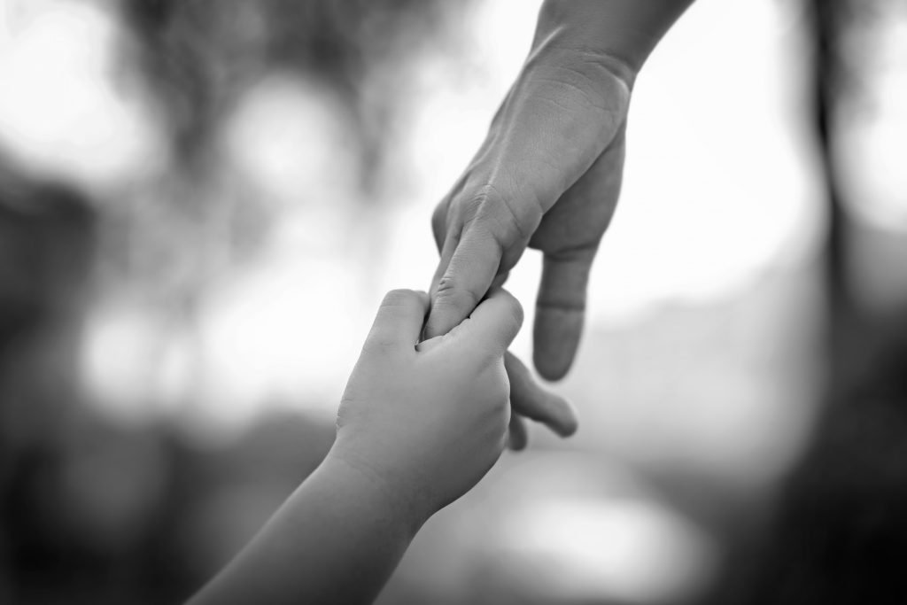 adult holds child's hand