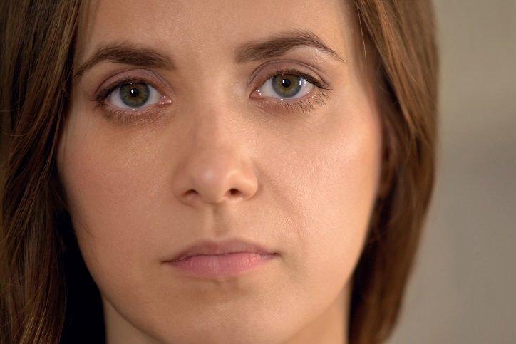 Serious young woman looking at camera, domestic violence victim, face closeup
